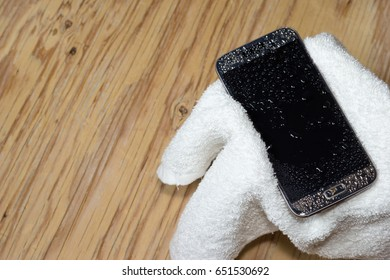 Hands holding White cloth with wet smartphone drops on wooden floor