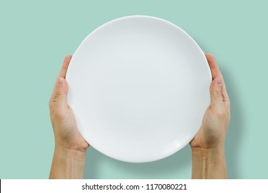 Hands are holding a white empty plate. Gastronomy and meal concept. Top view of an empty white plate on a pastel green background. Serving dinner at a restaurant.