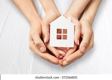 Hands holding hands holding white paper house.