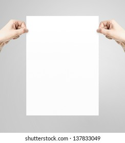 hands holding white paper poster