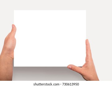 Hands holding white paper (sheet, board) tablet size with copy space. Tablet imitation.