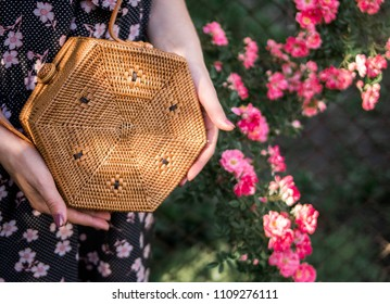 Hands holding wicker bag on the natural background