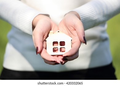 hands holding a wood house
