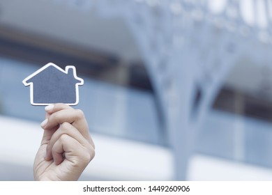 hands holding a wooden cut house on commercial house background