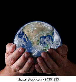Hands holding world with isolated black background. Earth image courtesy of NASA.