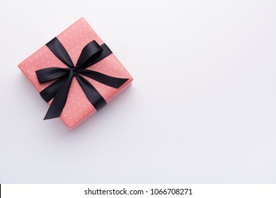 Hands holding wrapped gift box with colored ribbon as a present for Christmas, new year, mother's day, anniversary, birthday, party,  on white background, top view. Present for a colleague at work.