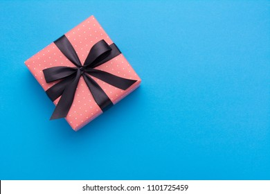 Hands holding wrapped gift box with colored ribbon as a present for Christmas, new year, mother's day, anniversary, birthday, party,  on blue background, top view. Present for a colleague at work.