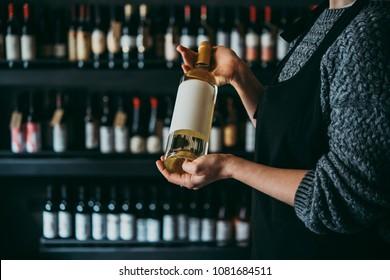 Hands holdong a wine bottle.