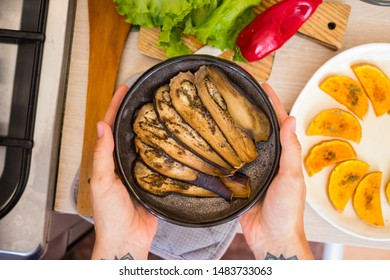 Hands holds baked aubergine, eggplant. Roasted with spices on plate. Vegan food
