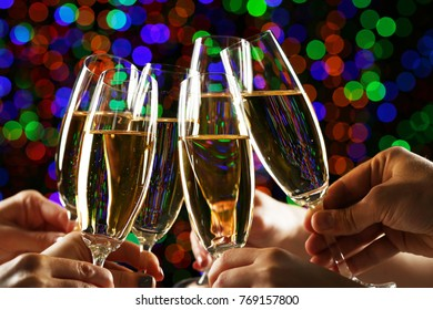 Hands holsing champagne glasses on lights background