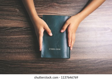 Hands with holy bible on the wooden desk.