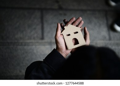 Hands of Homelessness Poor man holding  the paper house hope to  have family home and warm home , Home sweet home, uncertainty in life,  faith and hope concept,