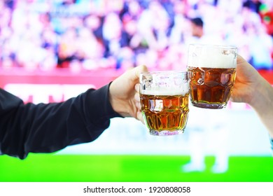 Hands horizontal holding lager beer glass and clinking on background of football game. Sport fans cheer up. Friends leisure lifestyle concept.