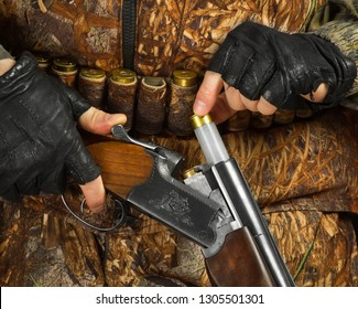 hands of hunter in camouflage loading the double-barreled shotgun for shooting, closeup