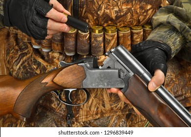 hands of hunter in camouflage loading shotgun, closeup