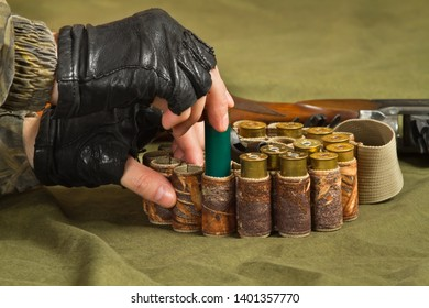 the hands of the huntsman fill his bandolier with hunting ammunition, closeup
