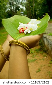 Hands of an Indian/Kerala girl with flowers on her palms. Prasada from Hindu temple