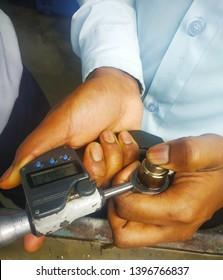 Hands with industrial micrometer gauge measuring work piece of cam shaft