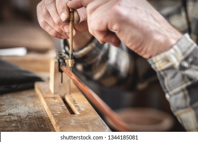 Hands of an instrument maker are manually drilling a tiny hole into a violin bow