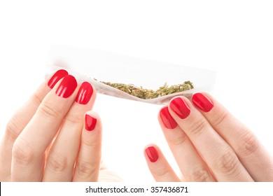 Hands isolated on white background rolling a cannabis joint. Smoking marijuana addiction. Feminine drug abuse.