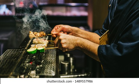 Hands of Japanese Yakitori Chef grilling chicken marinated with ginger, garlic and soy sauce and cucumber with a lot of smoke.