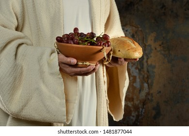 The hands of Jesus holding grapes and bread at Last Supper