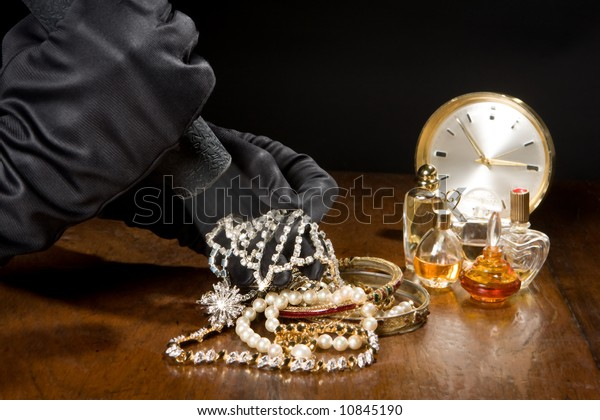 Hands of a jewelry thief with black gloves