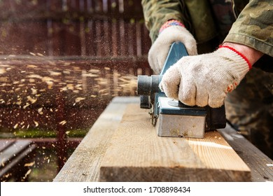 Hands of a joiner with an electric planer. Flying shavings, wooden board. The work of a professional. Woodwork.
