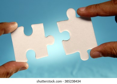 Hands joining jigsaw puzzle pieces