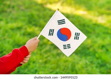 Hands of kid girl holding South Korea flag. Independence Day concept. Green grass background.