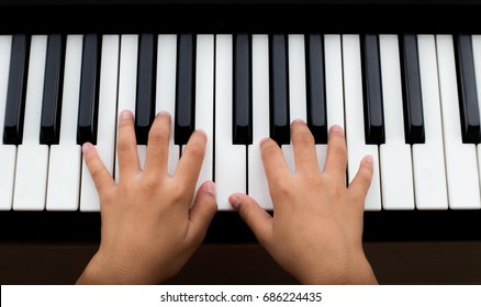 Hands of kid on piano keyboard