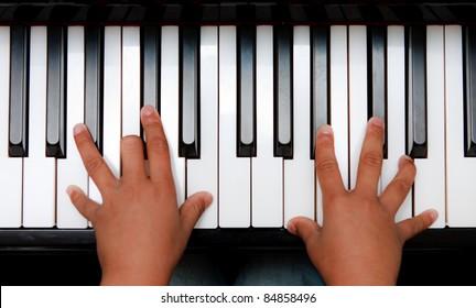 Hands of kid on piano keyboard