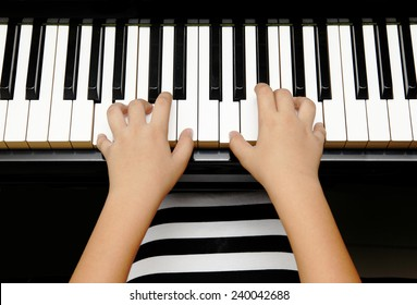 hands of kid playing piano