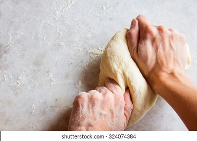 Hands kneading dough on white table