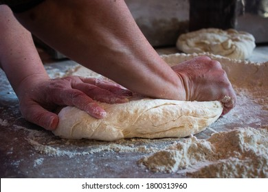Hands kneading dough over a wooden bakery table with flour around