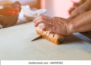 Hands with knife cut sushi. Sushi rolls on cooking board. Traditional uramaki sushi with salmon. New recipe from chef.