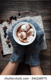 Hands in knitted mittens holding hot chocolate in grey heart cup with marshmallow and cinnamon, closeup