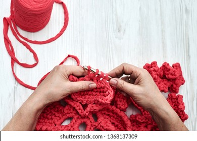 Hands knitting crocheting red flowers with thick rope threads on the table. Handmade process of crocheting.