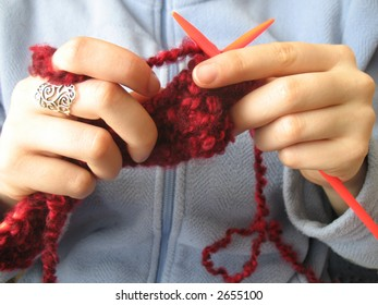 Hands knitting a red scarf on blue background