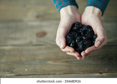 hands of a lady with full of dried plums on wooden background