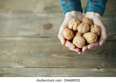 hands of a lady with full of walnuts on wooden background