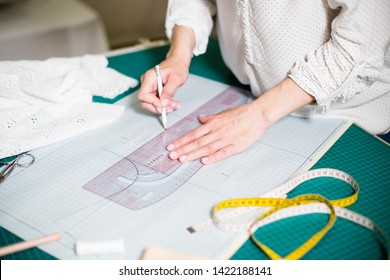 Hands of lady tailor working in her studio, tools and fabric samples on the sewing table