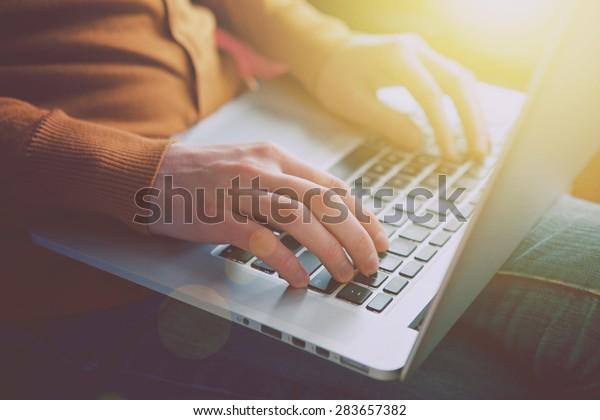 Hände mit Laptop-Schreibgerät in Sonnenlicht