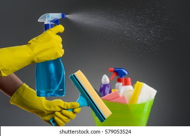 Hands in latex gloves using a spray and holding a window cleaning brush, slow motion, close-up. Plastic basin with liquid detergants, stain removers, a sponge, blurred. Dark neutral background.
