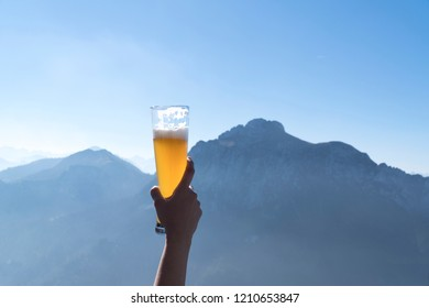 Hands lifting draft beer glass and happy enjoying harvest time at outdoor on beautiful mountain scene background.Celebration drinking beer.