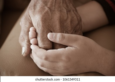 Hands of little Asian kids holding poor elderly grandfather man hands wrinkled skin with feeling care and Love. Father's Day and Family Older people concept