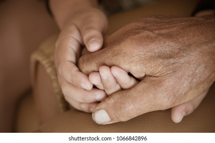 Hands of little Asian kids holding poor elderly grandfather man hands wrinkled skin with feeling take care of Love. World Kindness Day concept and Adult day care center, Relationship of Family concept