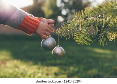 Hands of little boy decorating Christmas Tree outdoor