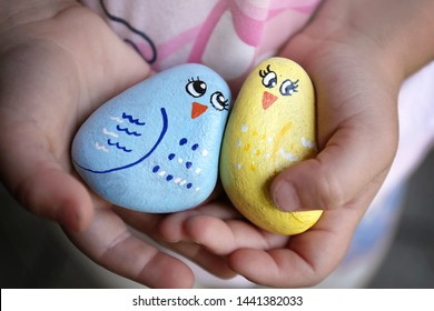 The hands of a little child are holding some Kindness Rocks painted like happy colorful birds.