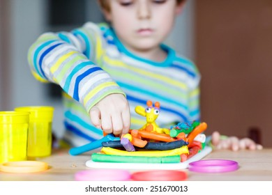Hands of little child playing with dough, colorful modeling compound, sitting at table at home or kindergarten, nursery. Creative leisure with kids.